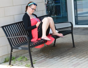 College student, comfortably parked  on this handsome bench, enjoys a read.