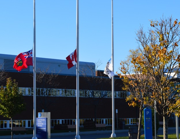 Flags are flying at half staff as a mark of respect for reservist  Corporal Nathan Cirillo who was murdered Wednesday while at his post at the National War Memorial in Ottawa. Pictured here is the scene outside the Welland campus of Niagara College. (Photo by Joe Barkovich)