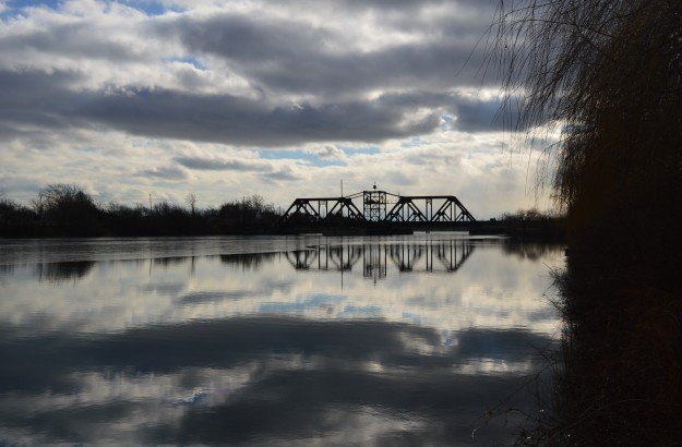 The old train bridge, a reflection of which can be seen in the Welland Recreational Waterway, makes a forlorn sight on a cold and partly overcast Tuesday afternoon. (Photo by Joe Barkovich)