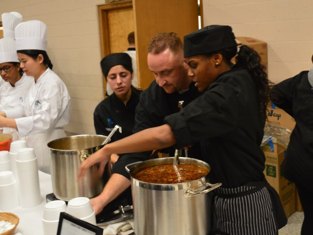 Lakeshore Catholic's soup prep team in action Friday at the Soup's On! fundraiser in Welland. From left: Rachel Khairallah, chef instructor Joe Fabiano and Akayla Brown. The team made minestrone. (Photo by Joe Barkovich)