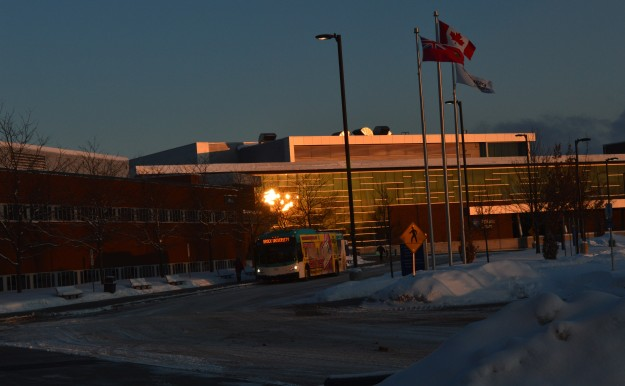 The sunrise reflects on the glass exterior of the college as an early-arriving bus rolls onto the campus about 7:15 a.m. (All photos by Joe Barkovich)
