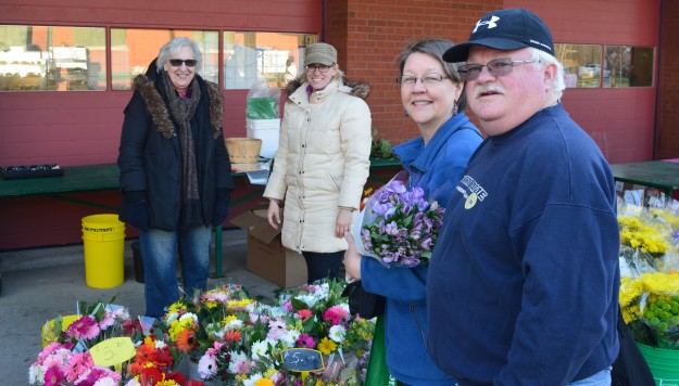 The Marshalls, Dan and Mary, have been market shoppers for years. Mary buys fresh flowers for  herself and her mother,  Anna Elders, every week from Aafke and Laura, background, of Pelham's Flower Man.