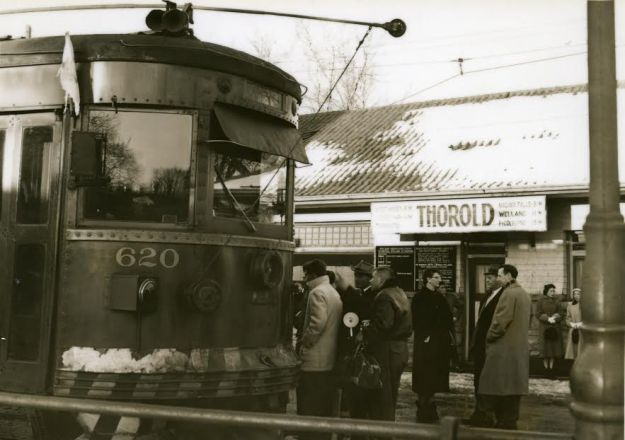 The final evening as people crowded  aboard the two cars at the station in Thorold. Note the huge sign with the distances to points  served even Toronto (by steamship I  assume, although that was not operating in 1959). Car #620 looks very polished and clean in the  late afternoon sun. (Supplied photo/Bob Chambers, Welland Tribune photographer, 1959)