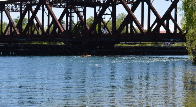The train bridge relic near the end of Sixth Street in Welland dwarfs a kayak that's about to pass beneath it on the recreational waterway early this afternoon. (Photo by Joe Barkovich. Out And About is a recurring feature on the blog.)