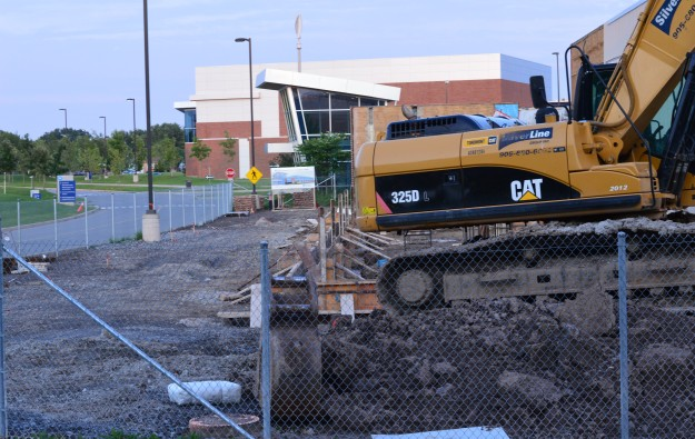 "This after-hours, evening view shows construction equipment idled. The building in the background is the college's athletic centre. Another excerpt from the magazine story: ""The Centre has been named in recognition of a $1.2 million contribution from Niagara's Walker family and its company, Walker Industries Holdings Limited. The contribution is the largest corporate donation in Niagara College history."" The ""need"" for this centre has been recognized by the province which stepped in with a $4.2 million investment toward its development, the magazine piece says."