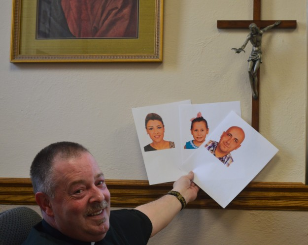 Father Gerard Power, O. Carm., holds images of the Syrian refugee family to be welcomed by his parish. (Photos by Joe Barkovich)