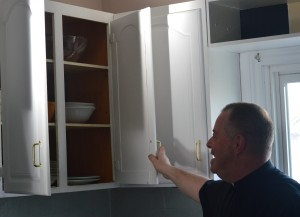 A kitchen cupboard with glassware, bowls other items gets a look of approval from the proud pastor.