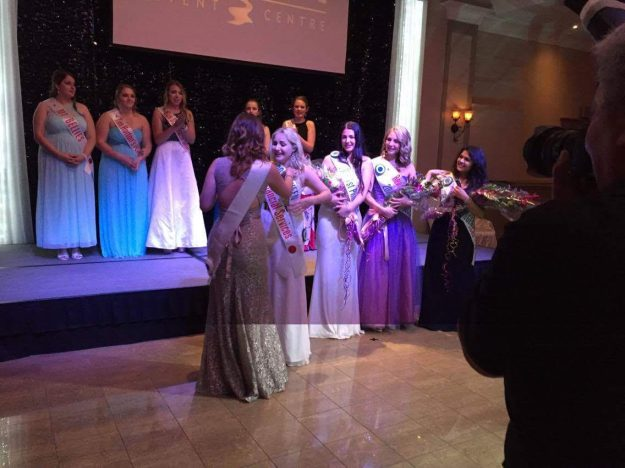 2015 Rose Queen Ashleigh Gisel, left, pins the sash on new Rose Queen Jen Marsh as members of the Royal Court, standing nearby, and the other contestants, on stage, watch.