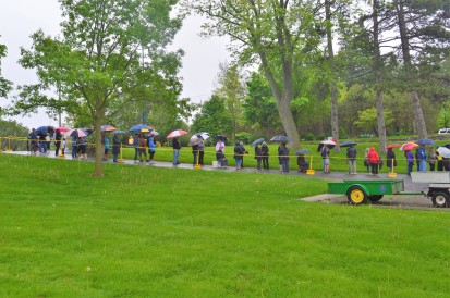 Showers early this morning couldn't dampen the spirits of these green thumbs, who turned out for the annual free, used tulip bulb giveaway in Chippawa Park by the city's parks department. Photos showing the lineups were taken just before the 8a.m. start time. Carm and Filomena Presti (backs to camera) stayed dry (for the most part) under a shared umbrella and saw the end of the line just ahead of them. Parks staffers Danny Gauthier and Kayla Crowe had bags with bulbs at the ready to distribute to the gardeners. The annual giveaway is a popular rite of spring here in the Rose City. (Photos by Joe Barkovich)
