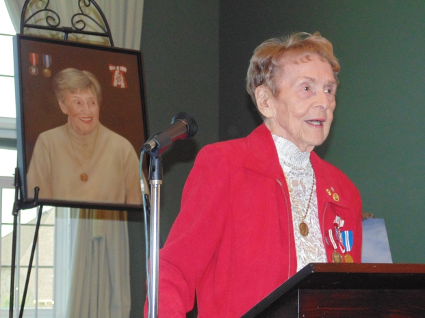 Dorothy Rungeling speaking, with Southwell's portrait positioned behind her. Details in story.