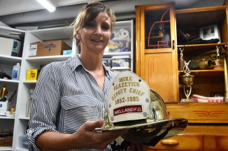 Marilyn Blazetich Sarkis, shown holding a commemorative helmet with her father's years of service, 1952-85. (Photos by Joe Barkovich)